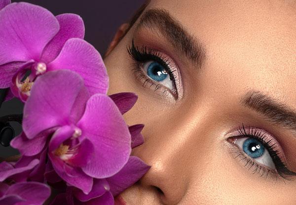 blue eyed woman beside deep pink flowers